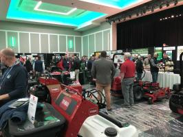 Attendees of the conference milling around turfgrass equipment.