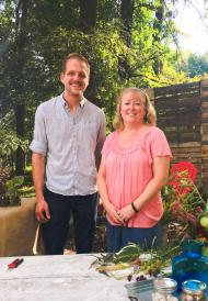 Aaron Steil and Cindy Haynes standing in front of a table with plants around them.