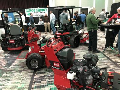 An image of the tradeshow floor, with attendees chatting and turfgrass equipment on display.
